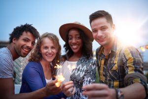 Multi-ethnic millenial group of friendsfolding sparklers on roof